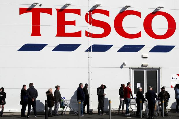 Largs and Millport Weekly News: People queue outside a Tesco Extra store in Madeley, Shropshire