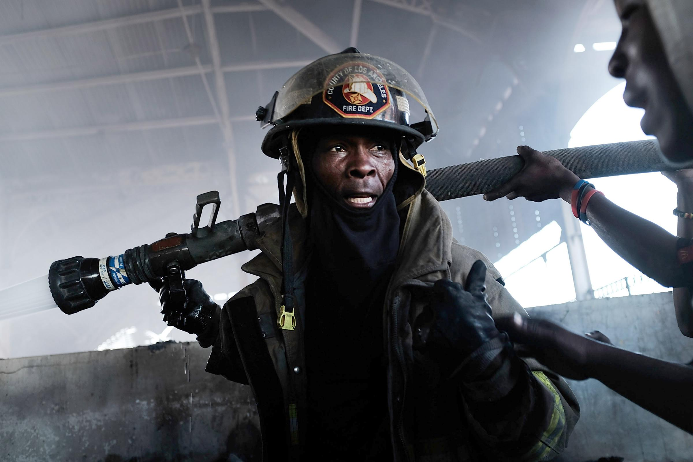 Firefighters work to put out a blaze at Port-au-Prince's historic Iron Market on February 13, 2018 in Port-au-Prince, Haiti