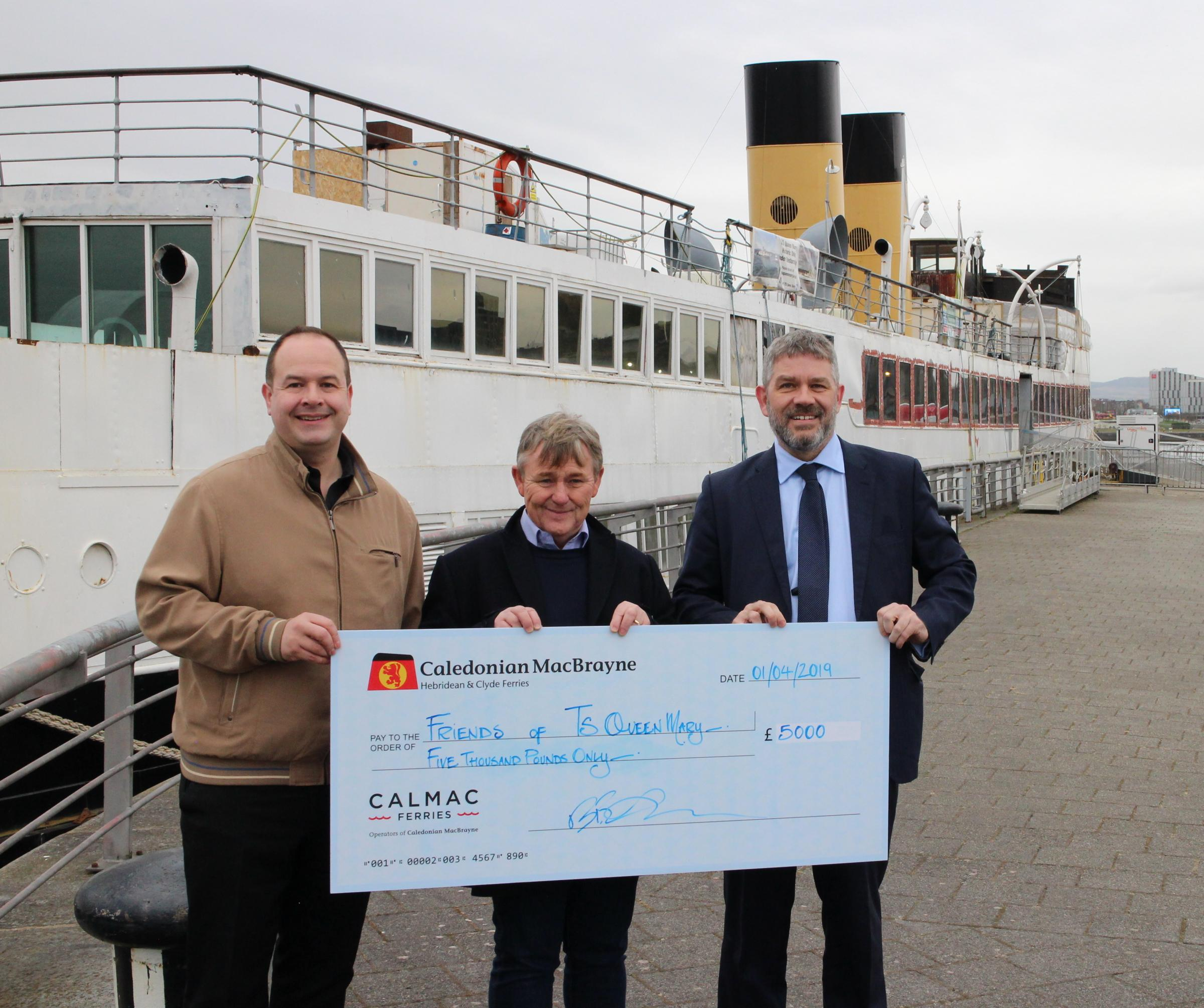 Cheque presentation:  CalMac's Director of Community and stakeholder Engagement, Brian Fulton (R) presents the cheques to Friends of Queen Mary trustees, Iain Sim (L) and Captain Calum Bryce.